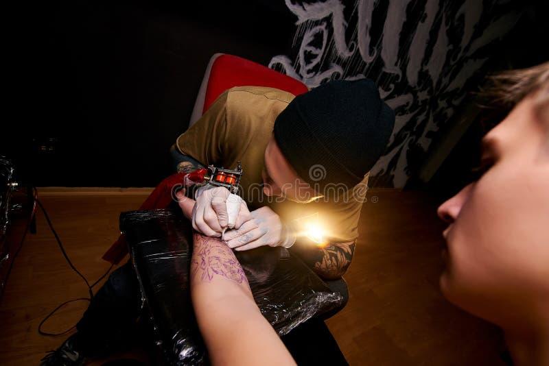 De knappe jonge kerel in een zwarte hoed en met tatoegeringen, slaat een tatoegering op zijn wapen, tatoegeringssalon stock foto's