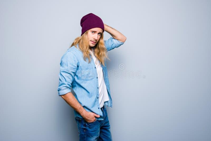 De knappe jonge kerel met stoppelveld, lang blondehaar, is binnen gekleed stock afbeelding