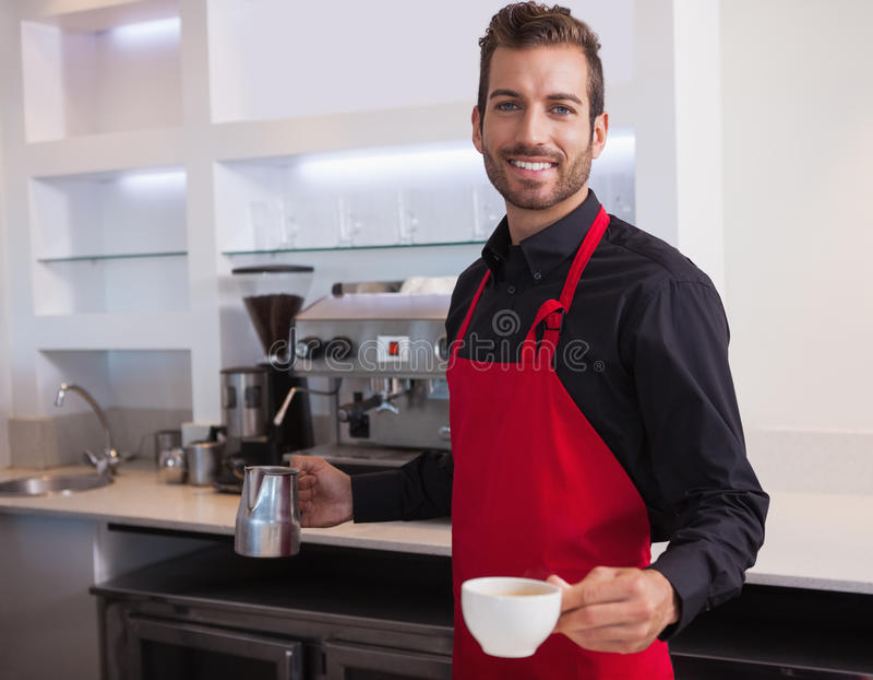De knappe jonge kruik van de baristaholding en kop van koffie stock foto's