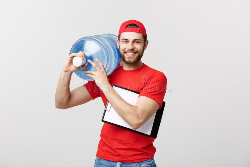 De knappe jonge leveringsarbeider in rode eenvormig houdt een fles water, bekijkt camera en glimlacht, op grijs stock fotografie