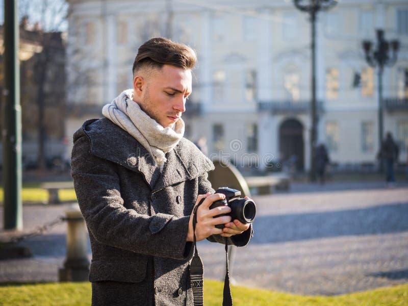 De knappe jonge mannelijke video van de fotograaffilm openlucht stock afbeelding