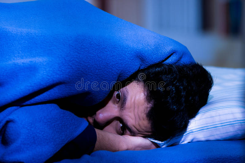 De knappe jonge mens in bed met ogen opende het lijden van slapeloosheid en slaap aan wanorde denkend over zijn probleem royalty-vrije stock afbeelding