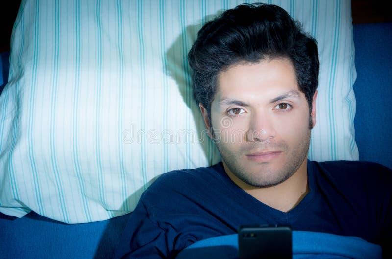 De knappe jonge mens in bed met ogen opende het lijden van slapeloosheid en slaap aan wanorde denkend over zijn probleem, boven m royalty-vrije stock afbeeldingen