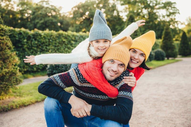 De knappe jonge mens brengt zijn vrije tijd met familie door, ontvangt greep van aanbiddelijke dochter en de mooie vrouw, heeft p stock fotografie