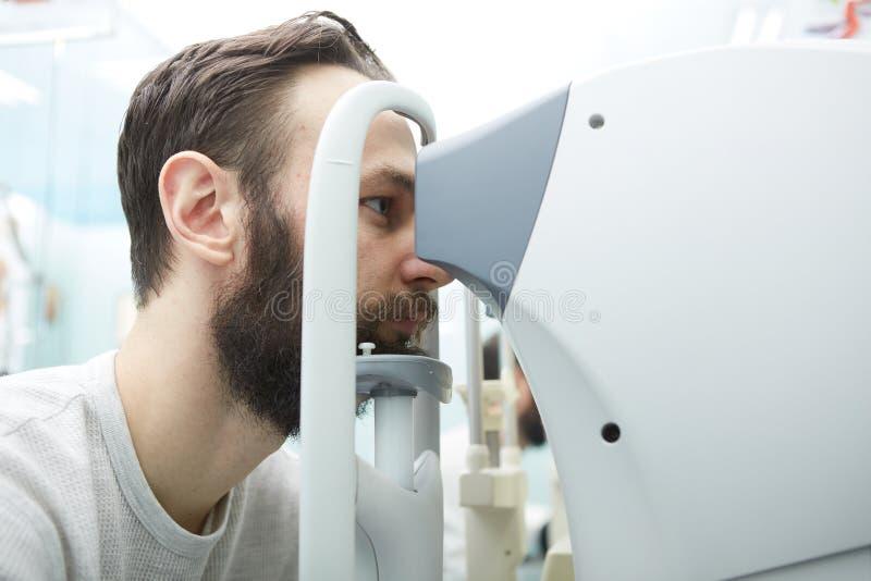 De knappe jonge mens controleert de oogvisie in moderne oftalmologiekliniek Patiënt in oftalmologiekliniek stock afbeeldingen