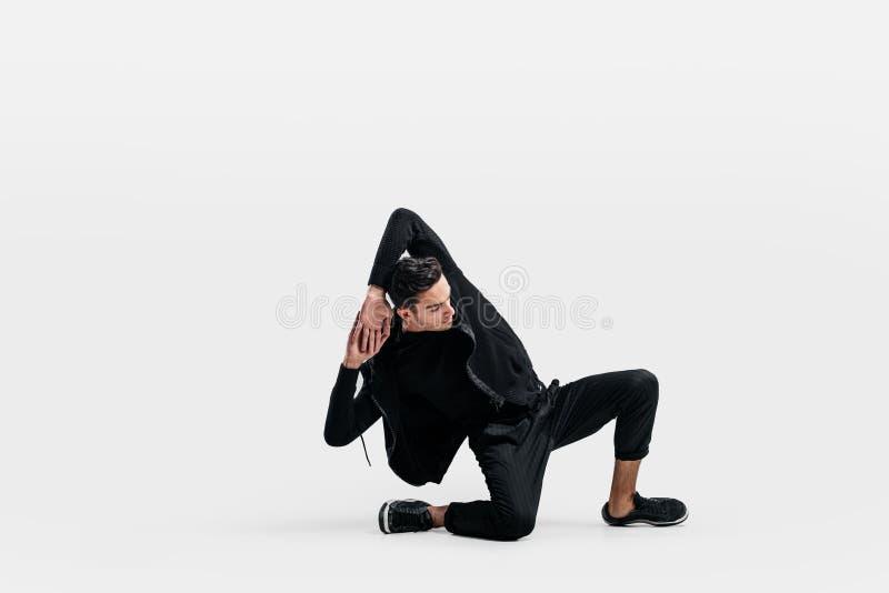 De knappe jonge mens die een zwart sweatshirt en een zwarte broek dragen is het dansen breakdance doend het dansen bewegingen op  stock afbeelding