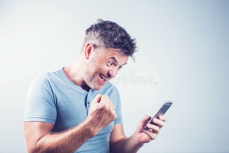 De knappe jonge mens die mobiele telefoon met behulp van voelt gelukkig stock foto