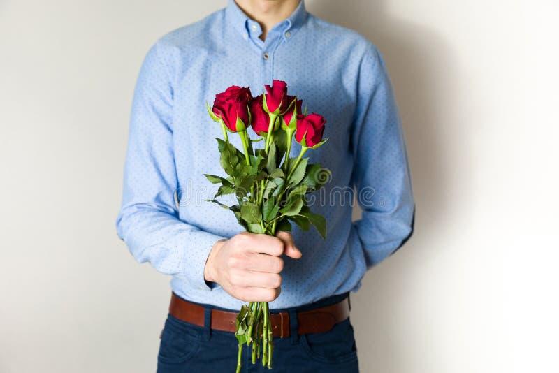 De knappe jonge mens die rood nam boeket, de romantische verrassing van de Valentijnskaartendag, liefde, bloemen houden toe stock foto