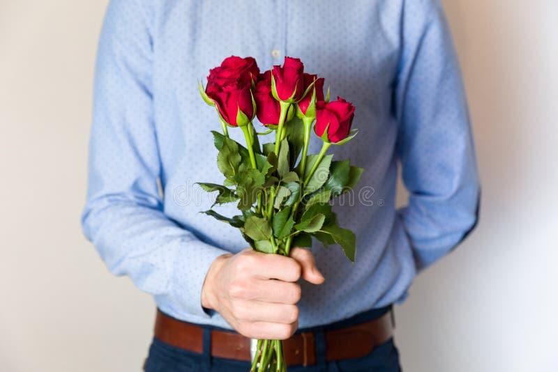 De knappe jonge mens die rood nam boeket, de romantische verrassing van de Valentijnskaartendag, liefde, bloemen houden toe royalty-vrije stock foto's