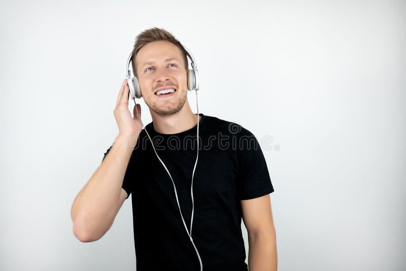 De knappe jonge mens die zwarte t-shirt dragen die aan muziek in hoofdtelefoons luisteren isoleerde witte achtergrond stock foto