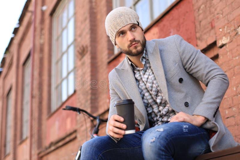 De knappe jonge mens in grijze laag en hoedenzitting op een bank ontspande het drinken koffie en het denken dichtbij zijn fiets stock fotografie