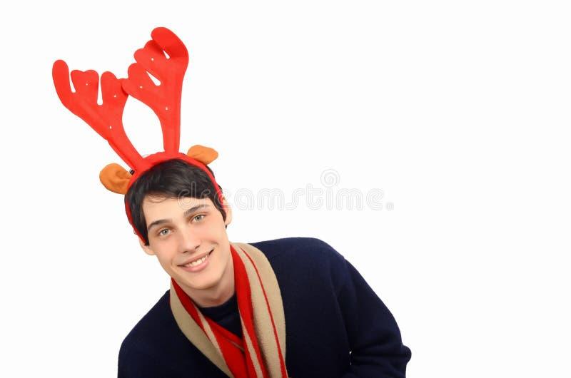 De knappe jonge mens kleedde zich voor Kerstmis, dragend rendierhoornen. stock fotografie
