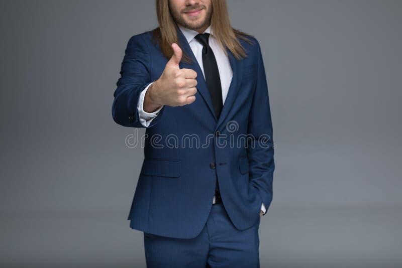 De knappe jonge mens in kostuum die duim tonen ondertekent omhoog stock afbeeldingen