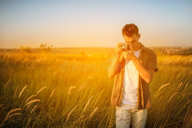 De knappe jonge reizigersmens met uitstekende camera, neemt een beeld van een weide Reisstemming fotografie royalty-vrije stock foto