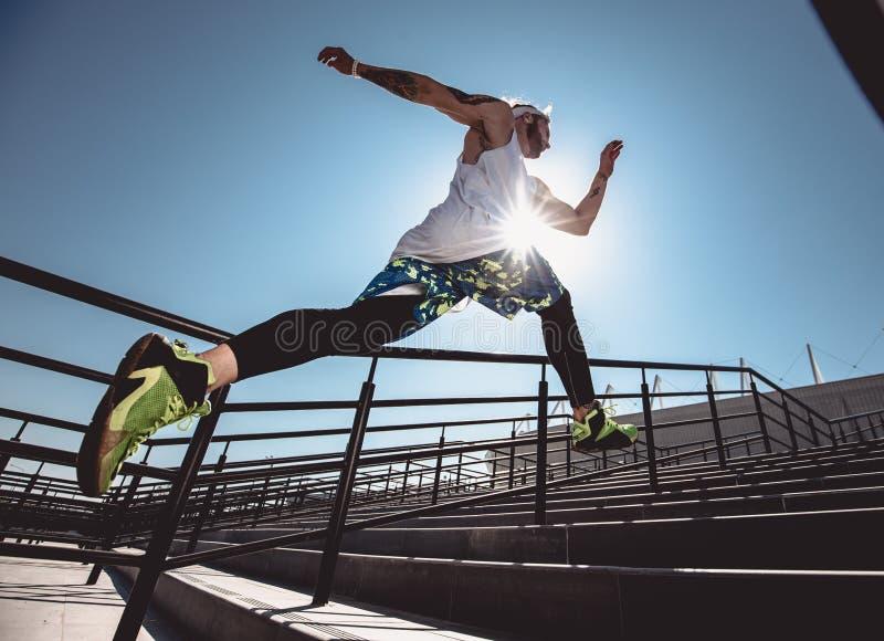 De knappe jonge spiermens in moderne sportkleding lanceert de treden openlucht bij heldere zonnige dag Brede hoekfoto van royalty-vrije stock fotografie