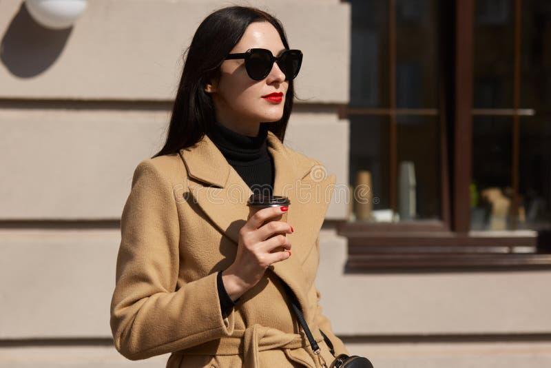 De knappe jonge vrouw houdt hete koffie in haar hand en geniet van warme zonnige dag, verse de lentelucht De aantrekkelijke aanbi stock afbeeldingen