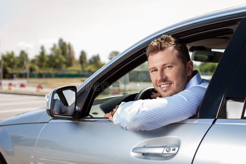 De knappe jonge zakenman drijft zijn auto royalty-vrije stock fotografie