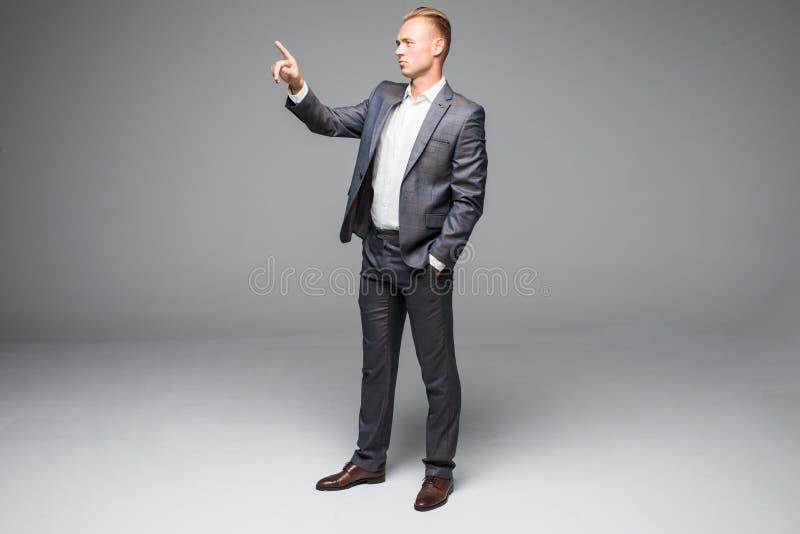 De knappe jonge zakenman duwt onzichtbare knoop op een grijze achtergrond royalty-vrije stock afbeeldingen