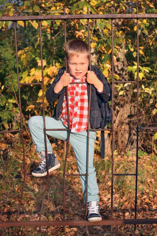 De knappe jongen in jeans beklimt op de omheining van het ijzerrooster stock afbeeldingen