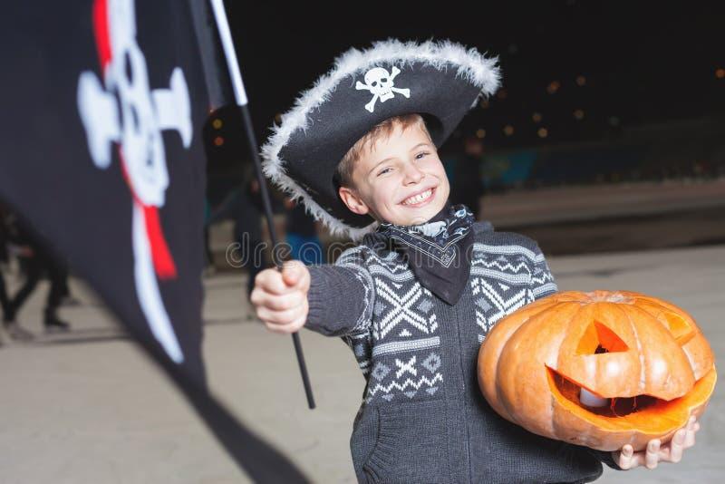 De knappe jongen kleedde zich in Halloween-piraatkostuum met vlag royalty-vrije stock fotografie