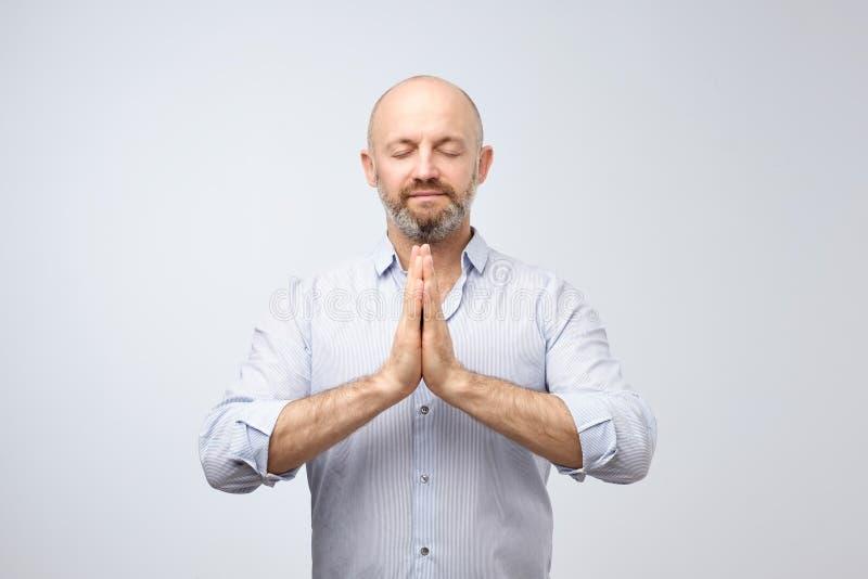 De knappe kale mens met varkenshaar die ogen houden sloot terwijl het mediteren, ontspannen voelen, vreedzame rust, royalty-vrije stock foto