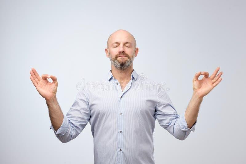 De knappe kale mens met varkenshaar die ogen houden sloot terwijl het mediteren, ontspannen voelen, vreedzame rust, stock afbeeldingen