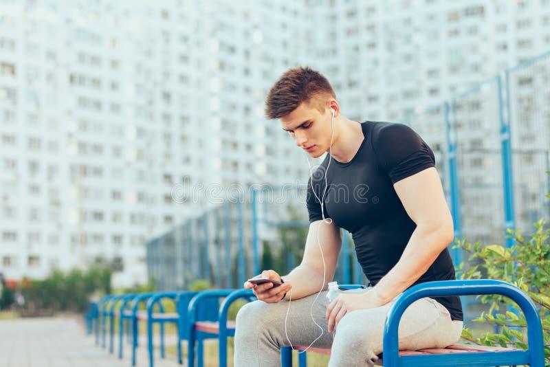 De knappe kerel in sport zwarte T-shirt en grijze sportbroek zit op bank op stad en stadionachtergrond Hij is royalty-vrije stock fotografie