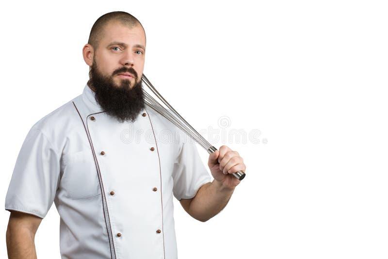 De knappe kokmens de handmixer dragen van de chef-kok eenvormige holding of de draad die zwaait Portret van gebaarde kok met eikl royalty-vrije stock fotografie