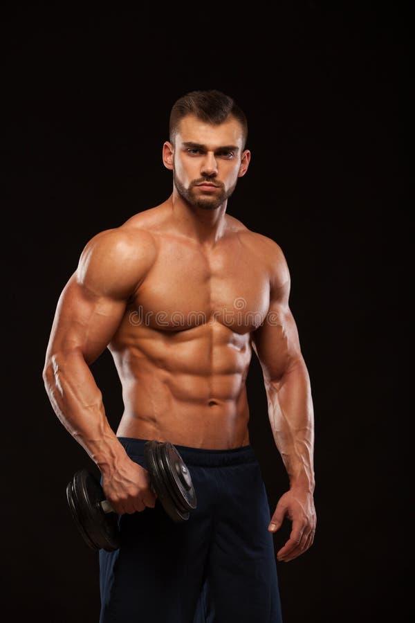 De knappe machts atletische mens met domoor kijkt vol vertrouwen vooruit De sterke bodybuilder met zes pakt, perfectioneert abs i stock foto's