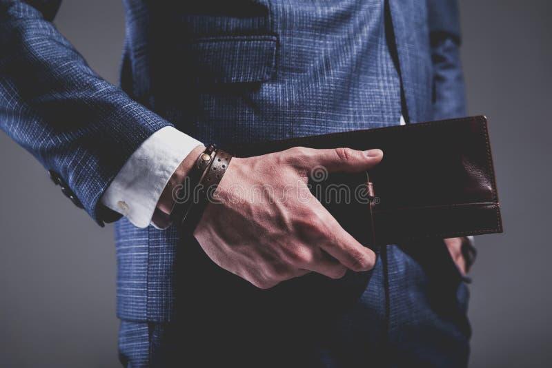 De knappe manierzakenman kleedde zich in elegant blauw kostuum op grijze achtergrond stock afbeeldingen