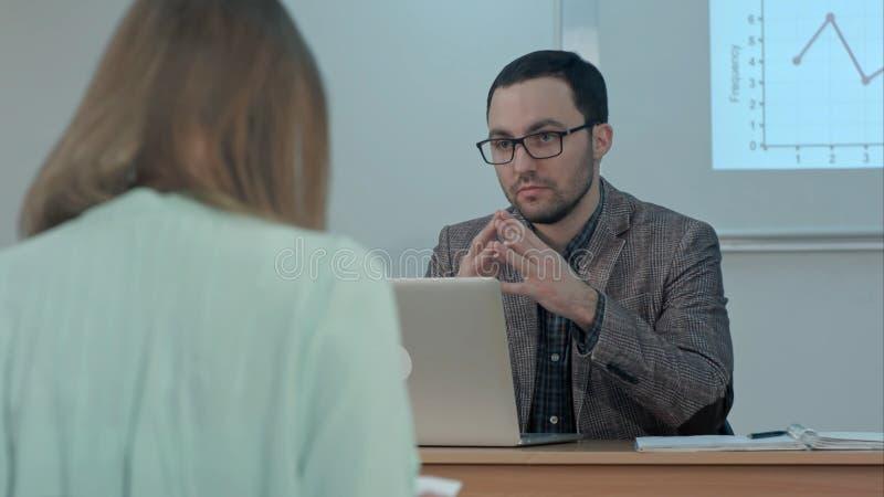 De knappe mannelijke leraar verklaart de klasse aan groep Spaanse studenten in klasse op school tijdens les royalty-vrije stock fotografie