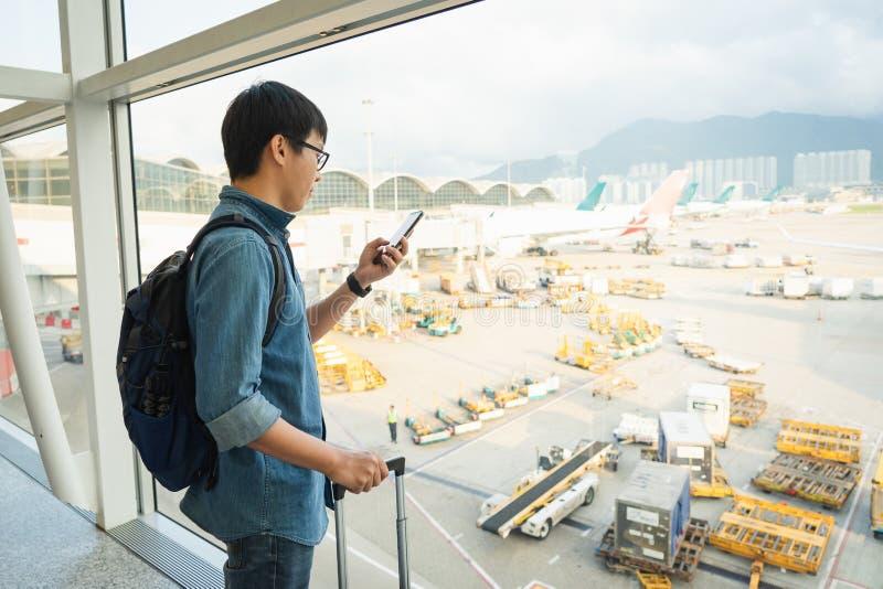 De knappe mannelijke toeristen gebruiken smartphones om vluchten te controleren alvorens in te schepen Het Gebruik van het reisco stock fotografie