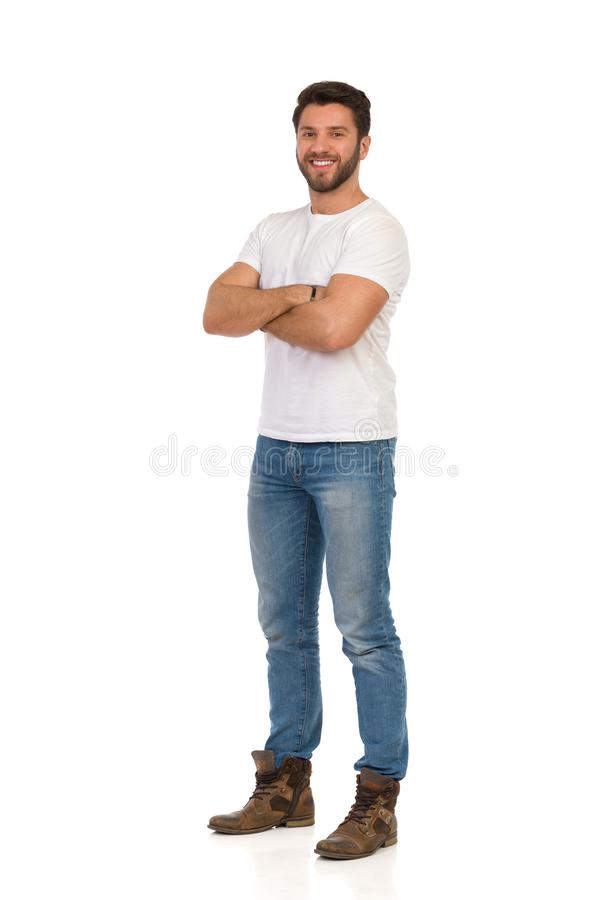 De knappe Mens in Jeans en Witte T-shirt bevindt zich met Gekruiste Wapens, glimlacht en bekijkt Camera royalty-vrije stock foto