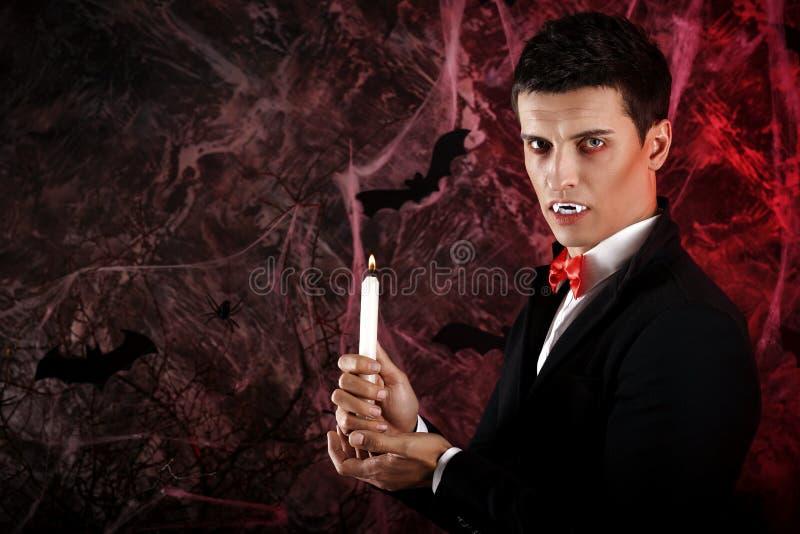 de knappe mens kleedde zich in een Dracula-kostuum voor Halloween stock afbeeldingen