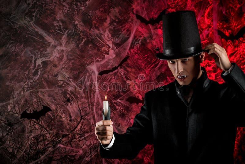 de knappe mens kleedde zich in een Dracula-kostuum voor Halloween royalty-vrije stock fotografie