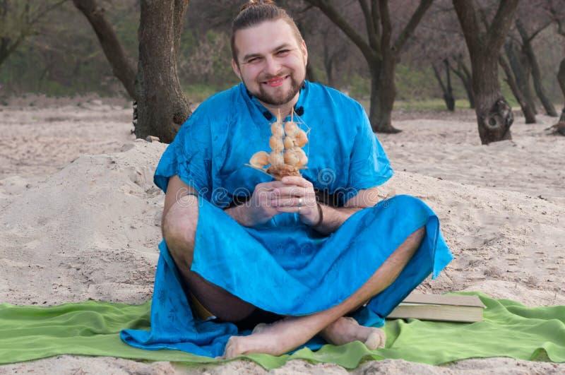 De knappe mens met maakt omhoog, de zitting van het haarbroodje op zand in blauwe kimono, het model die van het holdingsschip met stock afbeeldingen
