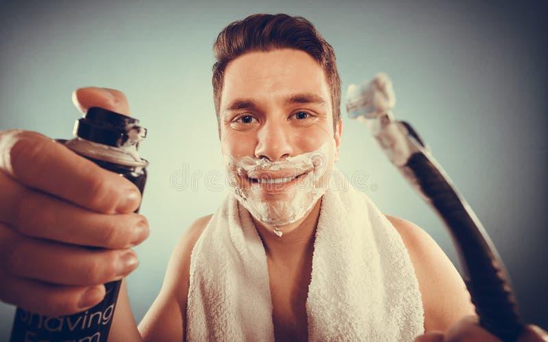 De knappe mens met scheercrèmeschuim kan en scheermes royalty-vrije stock foto