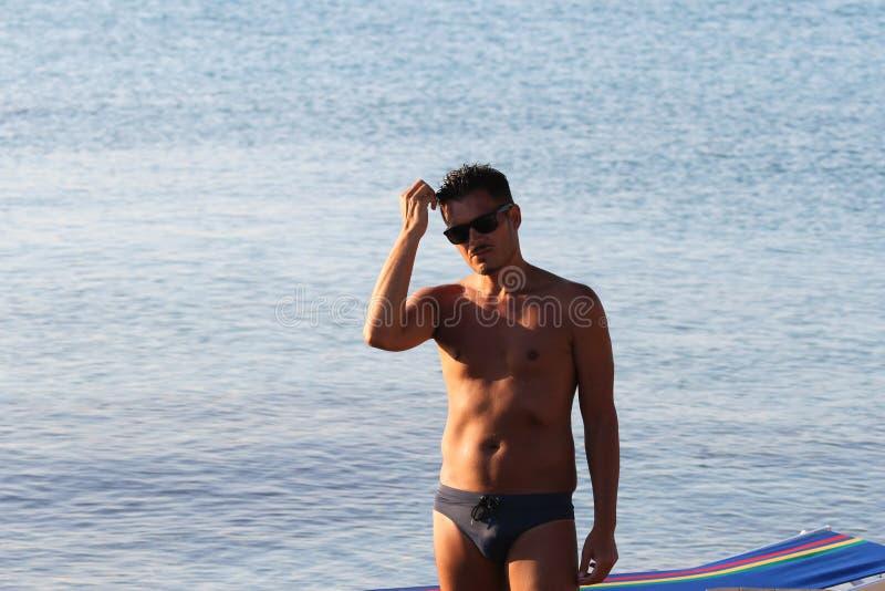 De knappe mens met zonnebril en het zwempak genieten van op het strand bij zonsondergang Apulia, Salento, Italië royalty-vrije stock foto