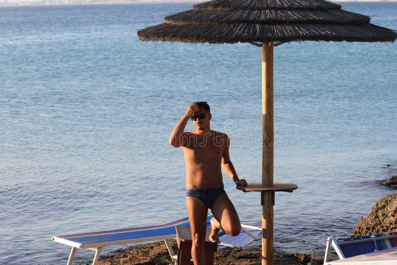 De knappe mens met zonnebril en het zwempak genieten van op het strand bij zonsondergang Apulia, Salento, Italië stock afbeelding