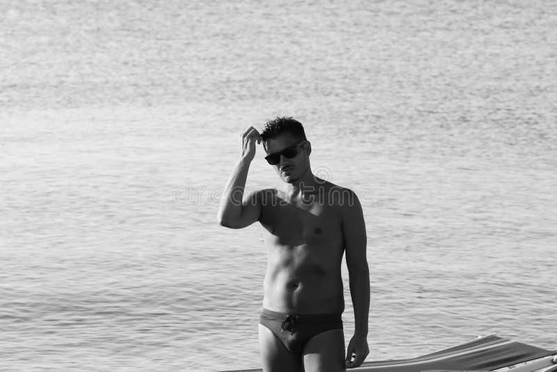 De knappe mens met zonnebril en het zwempak genieten van op het strand bij zonsondergang Apulia, Salento, Italië stock foto's