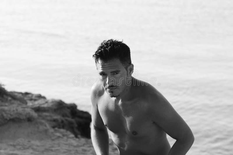 De knappe mens met zwempak geniet van op het strand bij zonsondergang Apulia, Salento, Italië royalty-vrije stock fotografie