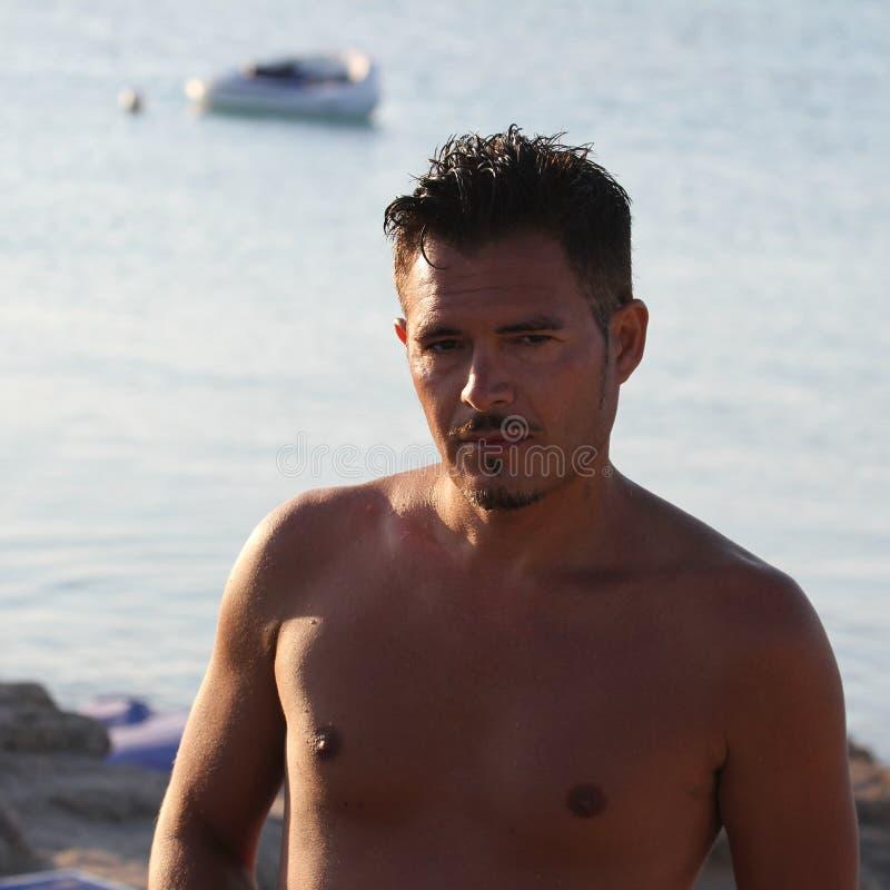 De knappe mens met zwempak geniet van op het strand bij zonsondergang Apulia, Salento, Italië royalty-vrije stock afbeelding