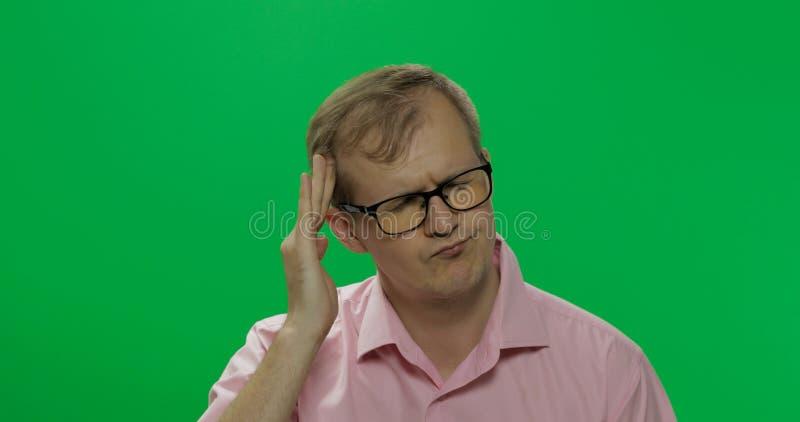 De knappe mens in roze overhemd heeft een hoofdpijn Twee in: 1 royalty-vrije stock afbeelding