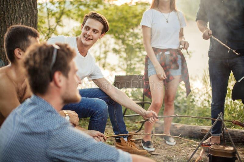 De knappe mens in T-shirt en jeans zit met stok onder vrienden stock foto's