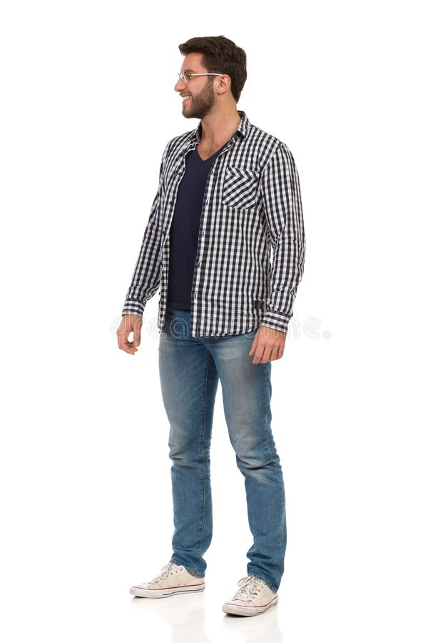 De knappe Mens in Tennisschoenen, Jeans, Houthakker Shirt And Glasses bevindt, kijkt zich weg en glimlacht stock afbeeldingen
