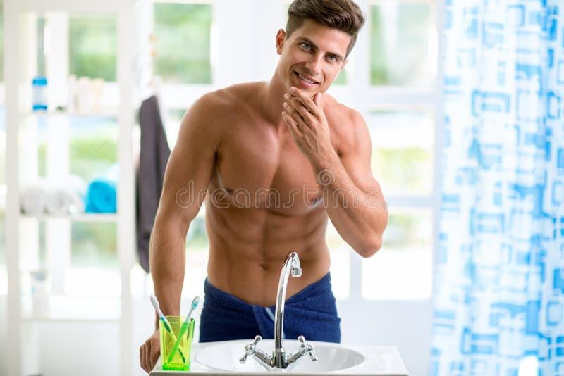 De knappe mens wordt weerspiegeld in de spiegel en controleert zijn baard stock foto