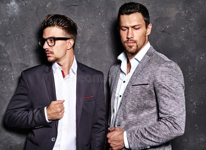 De knappe mensen van manier mannelijke modellen kleedden zich in elegante kostuums die dichtbij donkergrijze muur stellen stock afbeelding