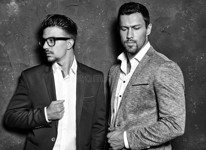 De knappe mensen van manier mannelijke modellen kleedden zich in elegante kostuums die dichtbij donkergrijze muur stellen stock fotografie