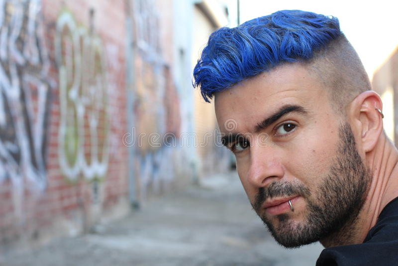 De knappe modieuze jonge mens met kunstmatig gekleurd blauw geverft haar ondergroef kapsel, baard en het doordringen met exemplaa stock fotografie