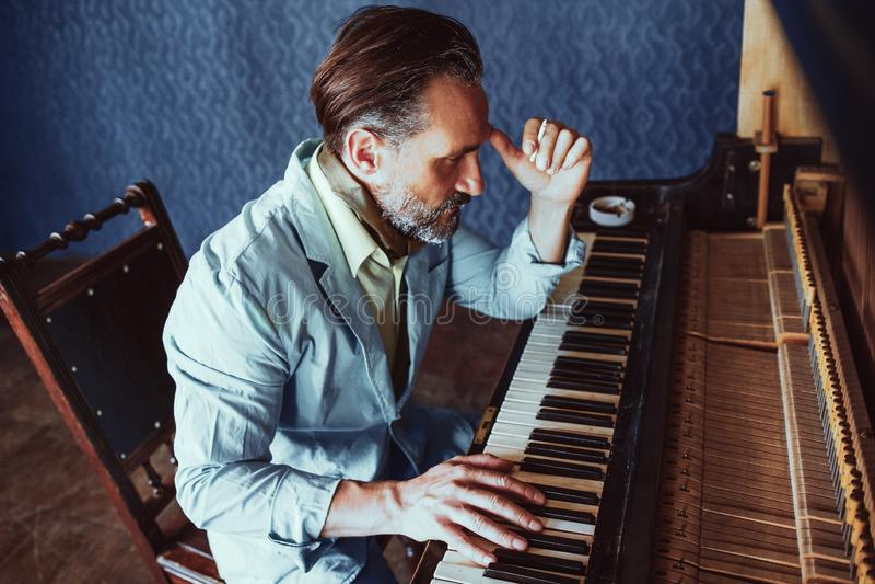 De knappe musicus stelt muziekzitting bij piano samen stock foto
